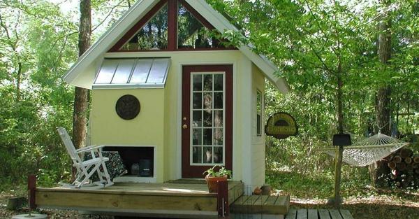 kleines-fertighaus-im-wald - ein weißer stuhl davor