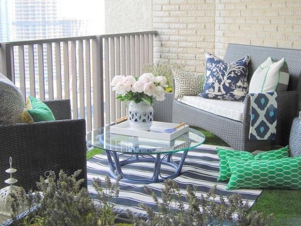 moderner-terrassenteppich-nesttisch -blumen in weiß und dekokissen