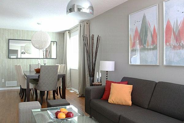schöner-wohnen-farben-dunkles-sofa-mit-einem-orangen-dekokissen-und-grauer-wand-mit-bildern
