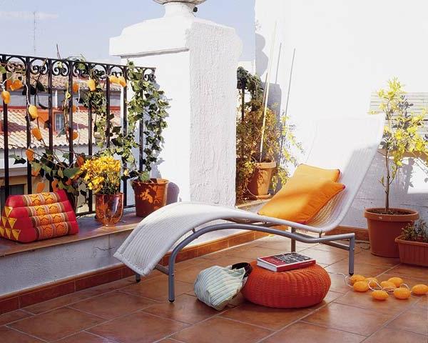 seitensichtschutz-balkon-weißer-liegestuhl-dekorative-kissen-in-orange