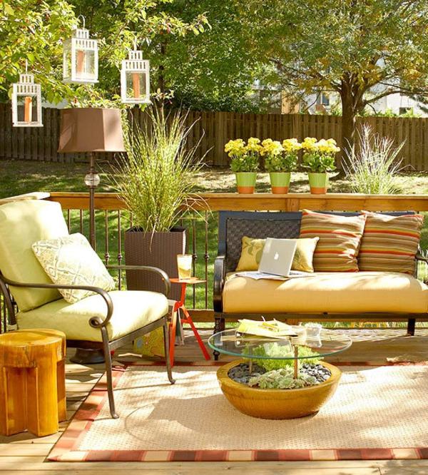 terrassenbelag-beige-farbe - zaun , grüne pflanzen und sofa mit kissen