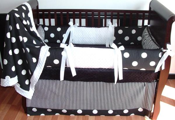 babybett mit bettbezügen in weiß und schwarz