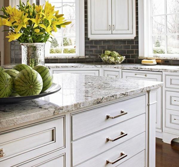 arbeitsplatte-aus-naturstein-für-die-küche- wassermelonen neben gelben blumen