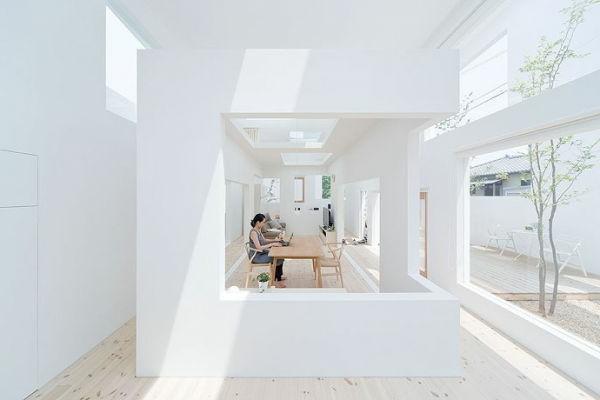 atemberaubende-minimalistische-architektur-in-weiß- eine sitzende frau