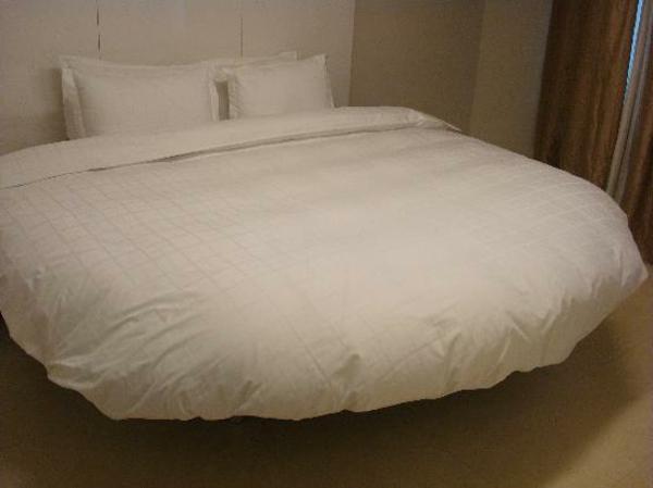 bett-mit-weißen-bettbezügen-schönes kleines schlafzimmer