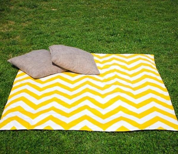 den-picknick-koffer-packen-gelbe-decke mit zwei dekokissen