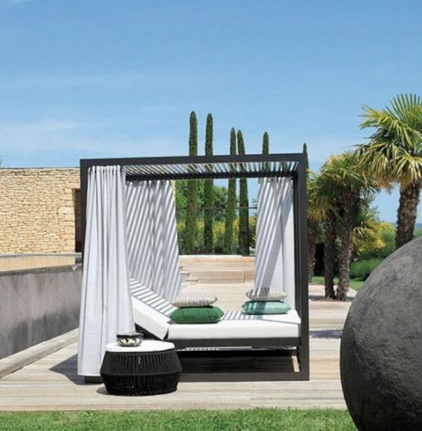 eko-haus-mit-einem-eleganten-outdoor-bett-mit-weißen-vorhängen-viele palmen