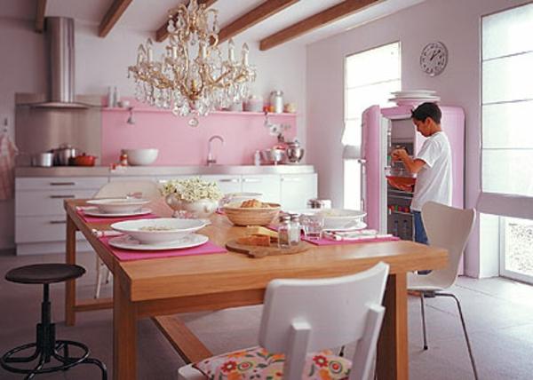 elegantes-esszimmer-mit-einem-großen-rosa-kühlschrank und ein lüster aus kristall
