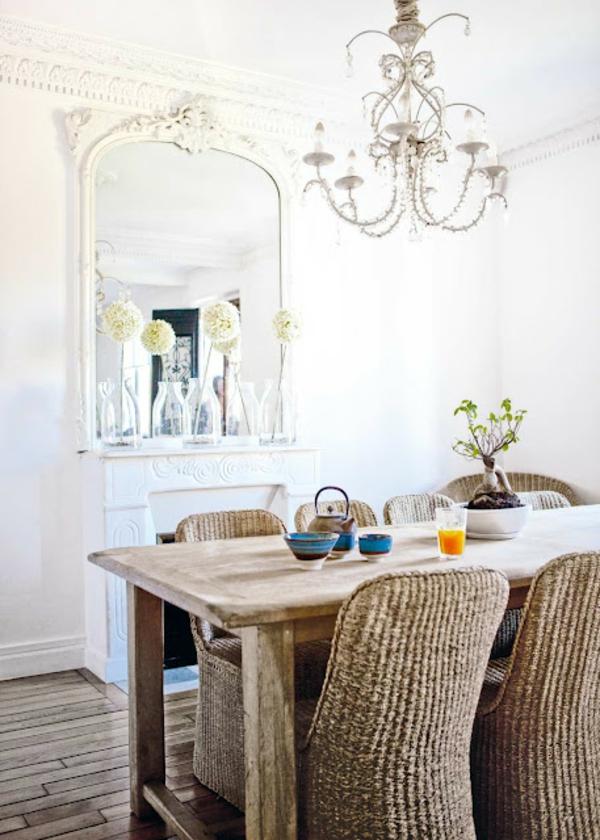 elegantes-esszimmer-mit-rattanmöbeln- weiße wand mit einem schönen spiegel