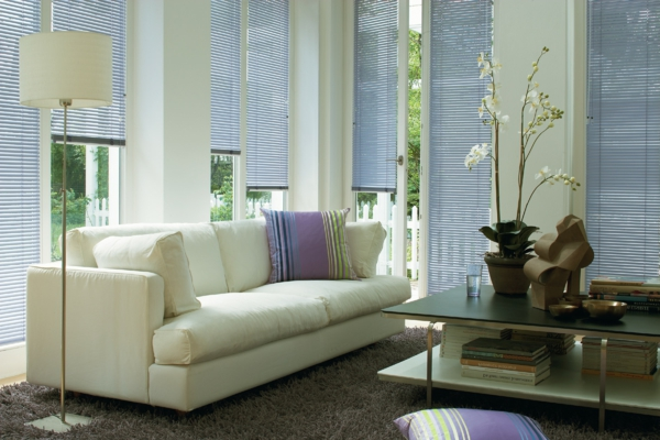 elegantes-wohnzimmer-moderne-jalosine- weiße stehende lampe neben einem sofa mit dekokissen