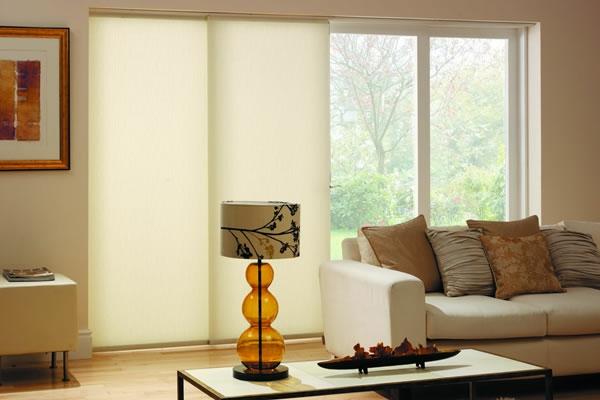 fensterjalousie- weißes sofa und dekokissen - eine moderne lampe daneben-moderne jalousien