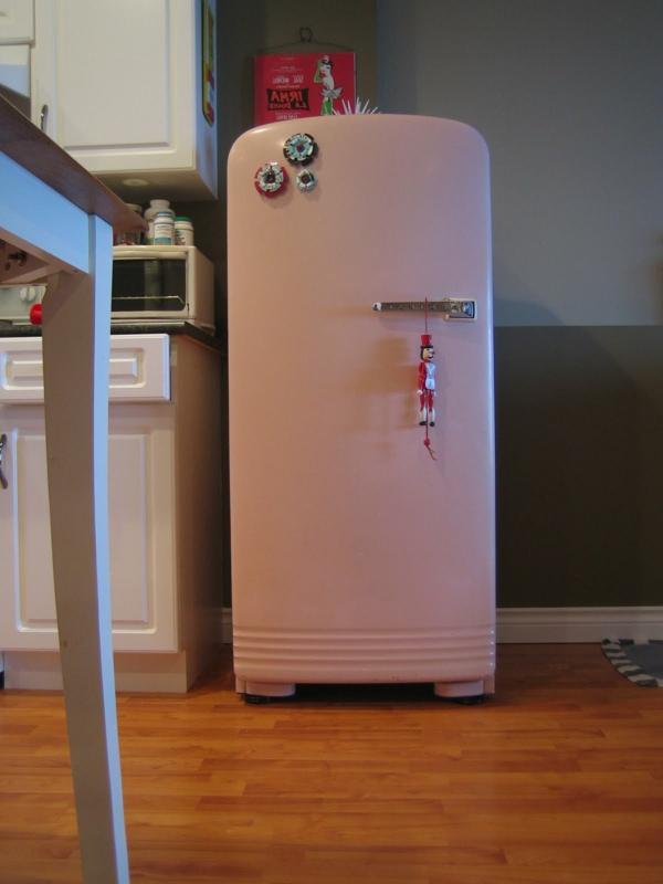 großer-rosa-kühlschrank neben einem weißen schank
