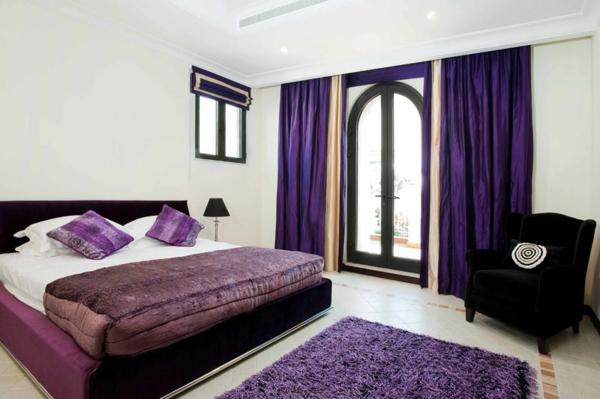 lila-schlafzimmer--bett-mit-dekokissen- schwarzer sessel
