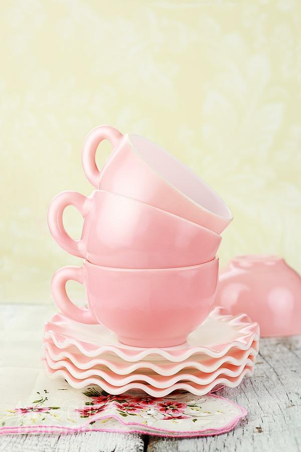 rosige-vintage-tassen-aufeinander-stellen- dahinter ist eine gelbe wand