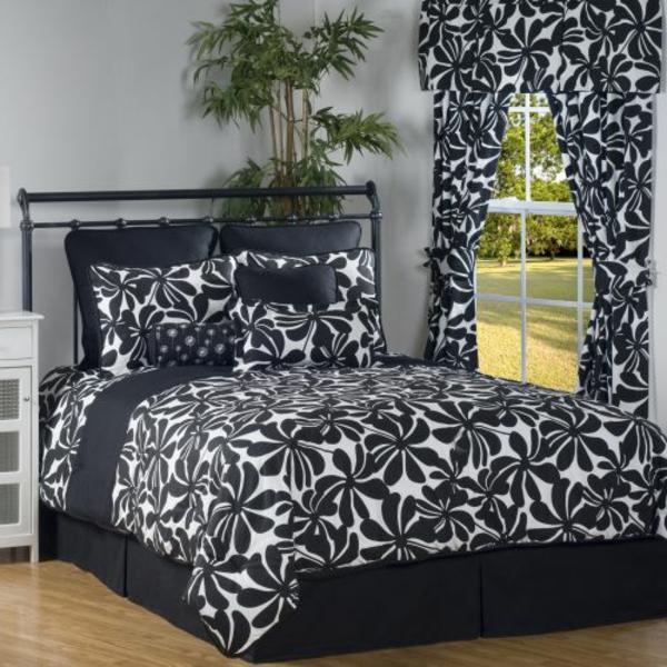 schlafzimmer-mit-modernem-bett-bettwäsche-in-schwarz-und-weiß-grüne pflanze