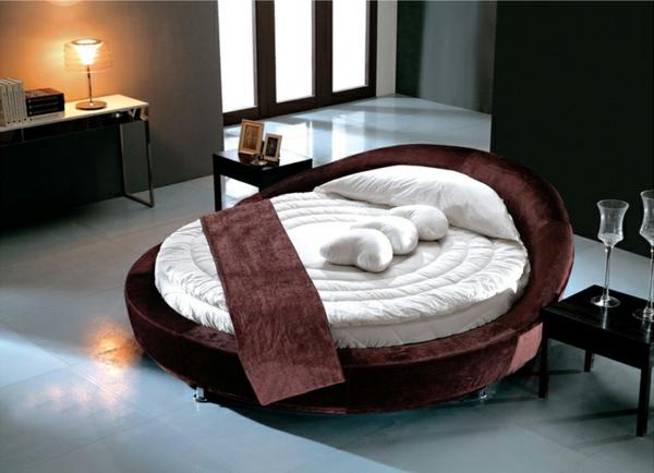 schlafzimmer--schönes-rundbett-eine lampe auf dem tisch