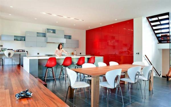 sehr-große-küche-viele-rote-barhocker- neben einem großen hölzernen massivtisch