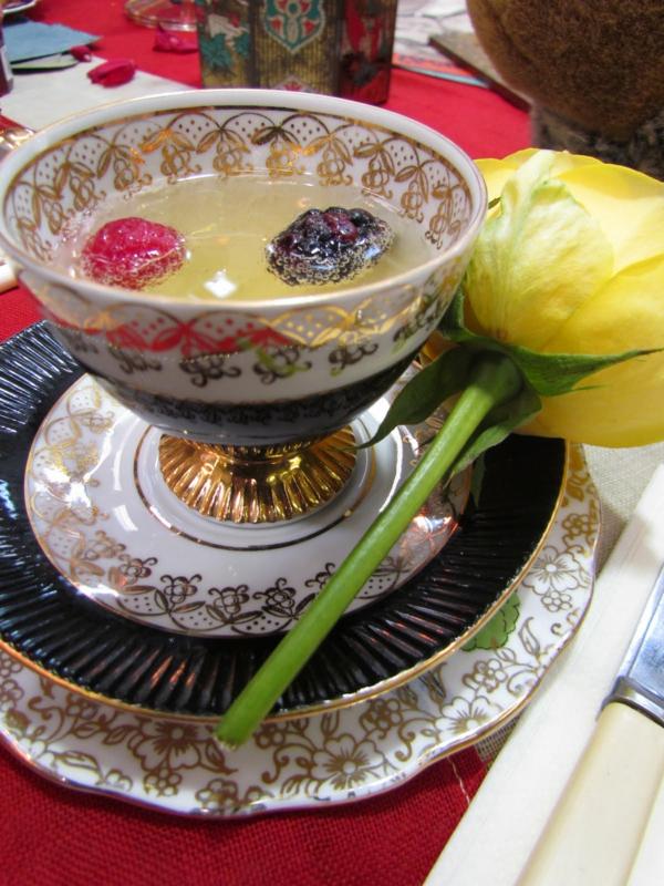 tasse-vintage-stil-eine-gelbe-tulpe-daneben- in der tasse sind eine himbeere und eine Maulbeere