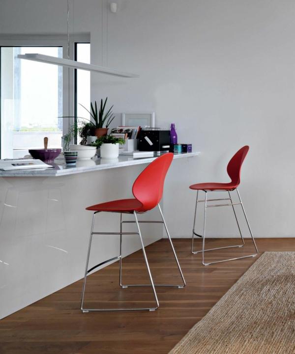 weiße-küche-und-rote-barhocker-neben einem braunen teppich