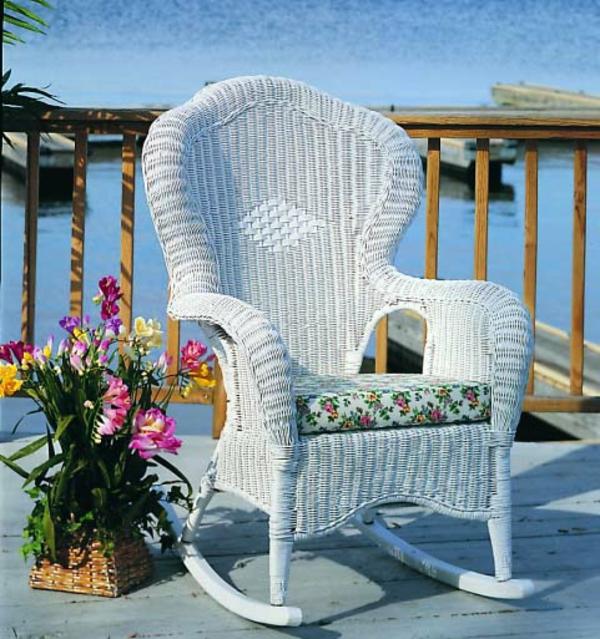 weißer-schaukelstuhl-aus-rattan-draußen-auf der terrasse