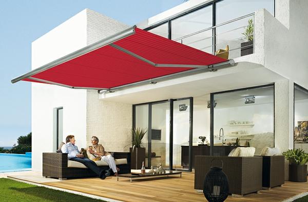 weißes-haus-und-rotes-sonnensegel-für-terrasse