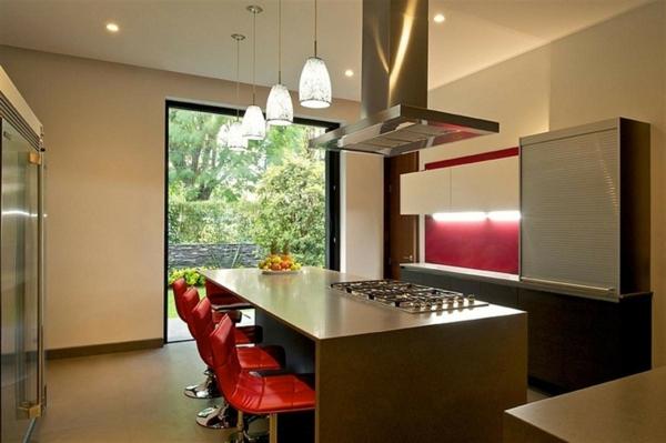 weitläufige-küche-und-barhocker-in-rot- gläserne wand und schöne hängende lampen