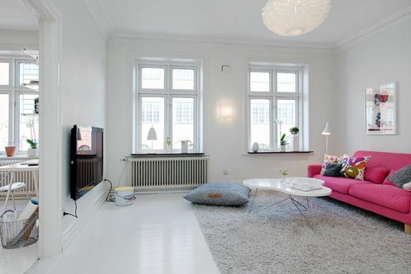 wohnzimmer-mit-einem-rosigen-couch-vor-dem-fernseher- weißes zimmer