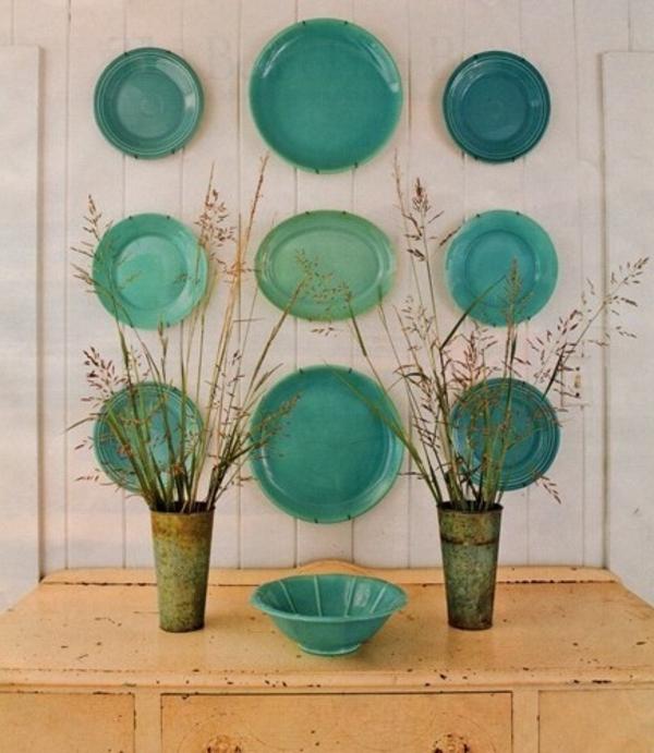 Küchenwandgestaltung-mit-sechs-grüne-teller-verschiedener-große-und-trockene-pflanzen