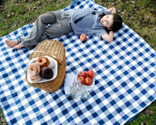 blaue-picknick-decke-ein mädchen liegt darauf