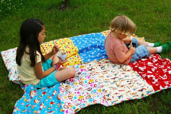 bunte-picknick-decke- ein mädchen und ein junge sitzen darauf