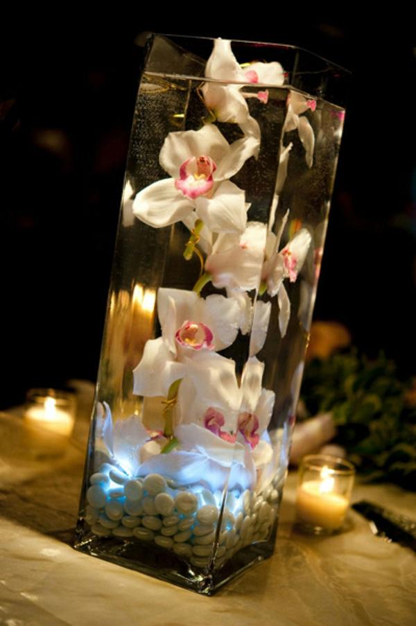 deko-mit-orchideen-im-gläsernen-becher-kleine kerzen daneben