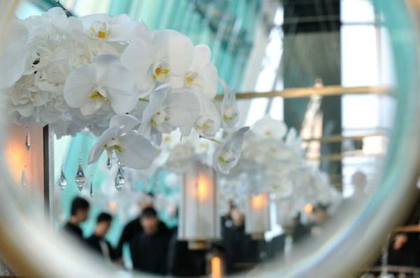 deko-mit-orchideen-weiße-farbe- und ein runder spiegel dahinter