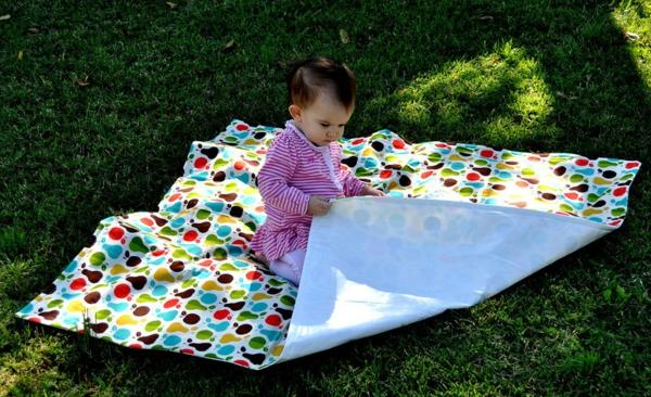 ein-baby-auf-einer-bunten-picknick-decke- super schönes foto