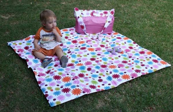 ein-kliener-junge-auf-einer-picknickdecke- in rosigen farbtönungen