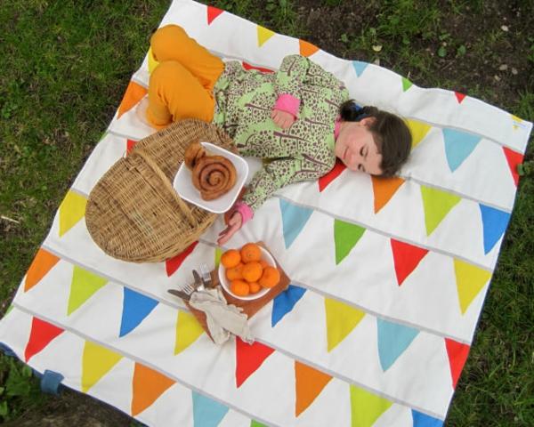 ein-mädchen-liegt-auf-einer-picknick-decke- foto von oben genommen