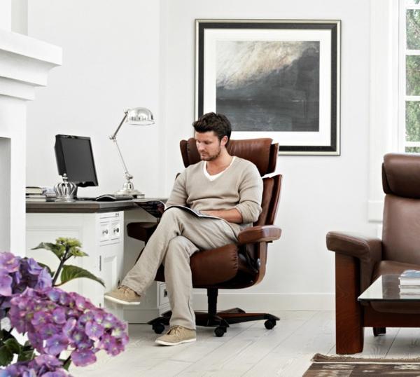 ein-mann-arbeitet-und-sitzt-auf-einem-stressless bürostuhl-ein großes bild dahinter