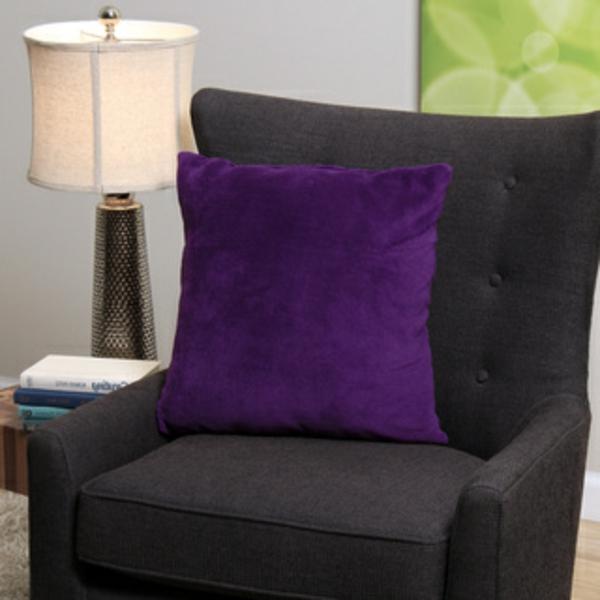 ein-schwarzer-sessel-mit-dekokissen-in-lila- neben einer lampe