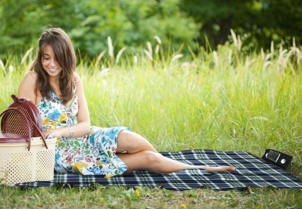 eine-hübsche-frau-auf-einer-picknick-decke- schöne natur-umgebung