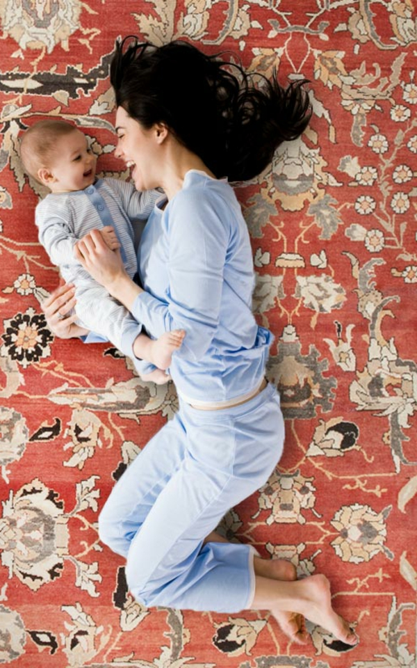eine-mutter-mit-einem-baby-auf-einem-retro-teppich- foto von oben gemacht