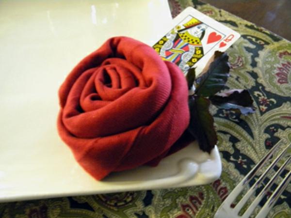 eine-rote-rose-aus-servietten-falten- eine spielkarte daneben