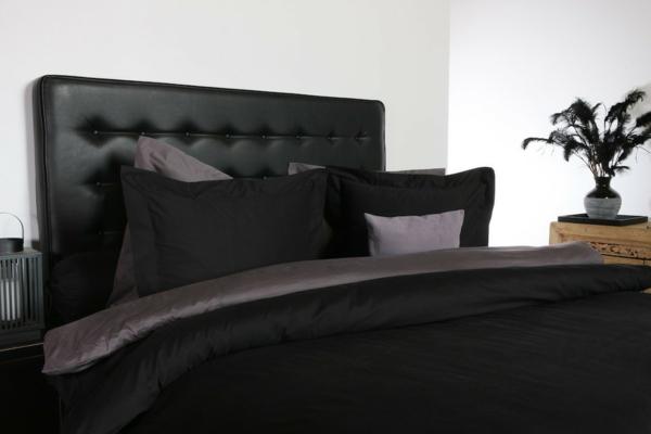 elegante-schwarze-bettwäsche- und kopfbrett eines bettes