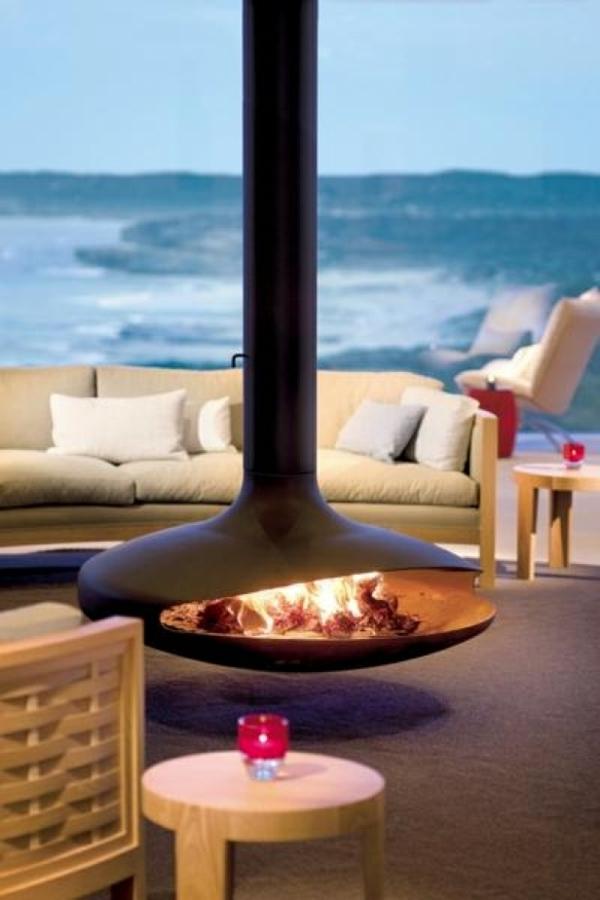 eleganter-hängender-kaminofen- ein sofa mit dekokissen dahinter