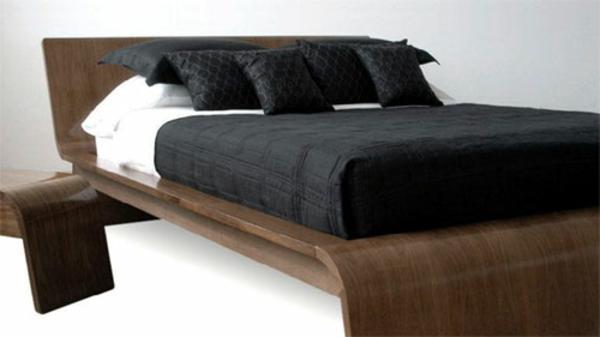 elegantes-skandinavisches-bett-mit-schwarzen-bettwäschen-hintergrund in weiß