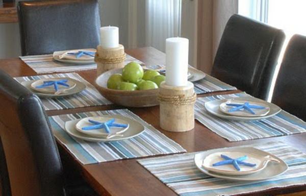 esstisch-mit-äpfeln-als-dekoration- zwei große weiße kerzen