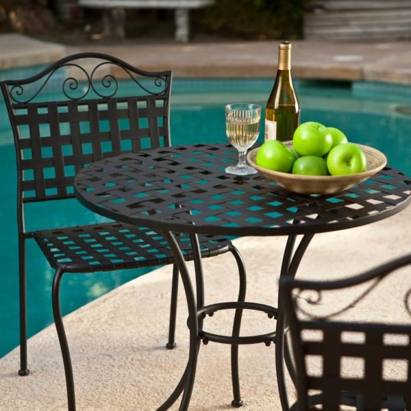 gartenmöbel-aus-eisen-grüne-äpfel-auf-dem-tisch- neben dem pool