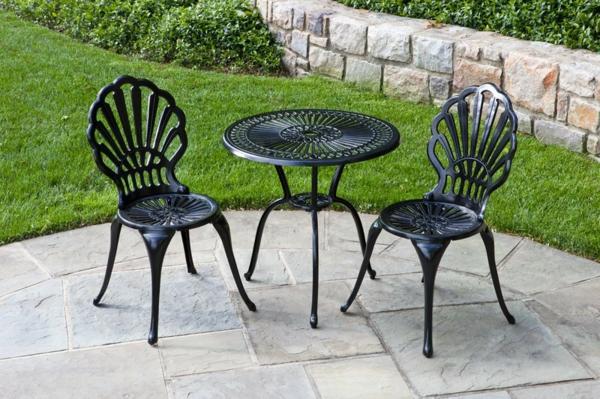gartenmöbel-aus-eisen-tisch-mit-zwei-stühlen- umgeben vom grünen gras und stein