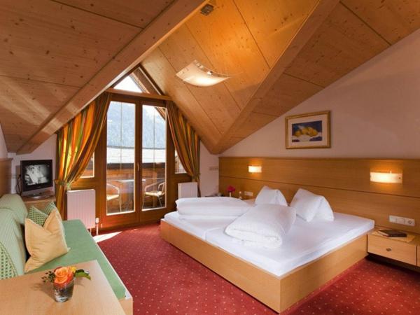 gemütliches-schlafzimmer-im-Dachgeschoss-mit-rottem-Teppich