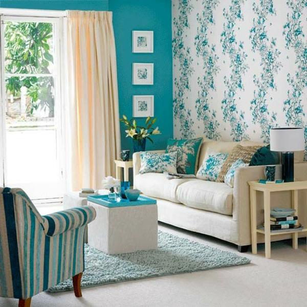gemütliches-wohnzimmer-mit-türkis-wandfarbe-und-müstertapete-und-bunten-kissen