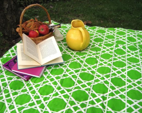 grüne-picknick-decke- ein geöffnetes buch und ein korb darauf