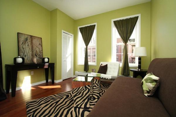 grüntöne-wandfarbe-braunes-sofa-und-zebra-teppich-auf-dem-holzboden